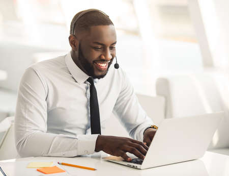 ハンサム スーツとヘッドセットでアフロ アメリカ人実業家がオフィスでノート パソコンで作業しながら笑みを浮かべてください。 写真素材