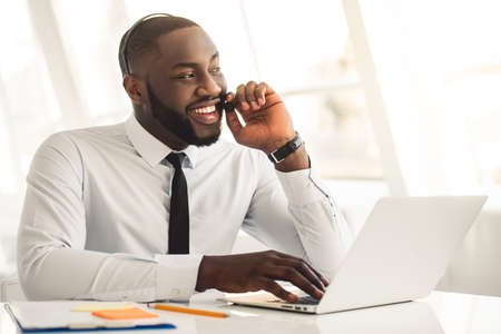 Handsome Afro American businessman in suit and headset is talking and smiling while working with laptop in office