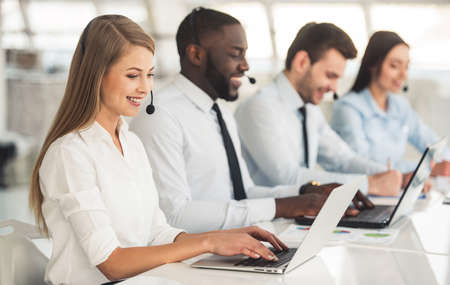 Attractive business people in suits and headsets are smiling while working with laptops in office
