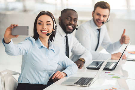 Attractive business people in suits and headsets are smiling while working with laptops in office. Girl is doing selfie