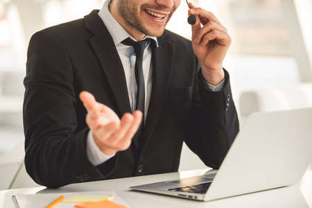 Cropped image of attractive businessman in suit and headset talking and smiling while working with laptop in office