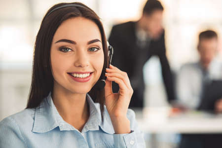 Attractive business woman in headset is smiling while working in office, her colleagues in the background Stock Photo