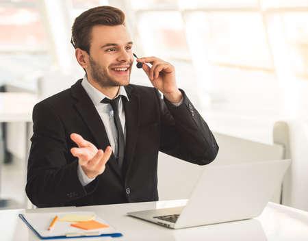魅力的なビジネスマンのスーツとヘッドセットが話しているし、オフィスでノート パソコンで作業しながら笑みを浮かべて
