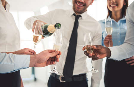 Cropped image of successful business people drinking champagne, talking and smiling while celebrating in office Фото со стока