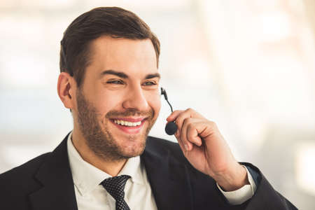 Handsome businessman in suit and headset is talking and smiling while working in office Stock Photo