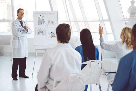 ハンサムな成熟した医師は、ホワイト ボードとスキームを使用して彼の同僚の講義を与えています。