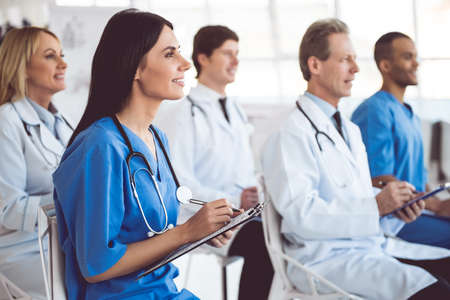 Successful medical doctors are making notes and smiling while sitting at the conference