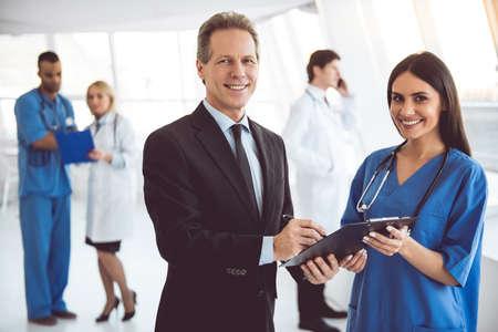 ハンサムな中高年ビジネスマンと美しい若い医師がカメラ目線と病院のホールに立ちながら笑顔