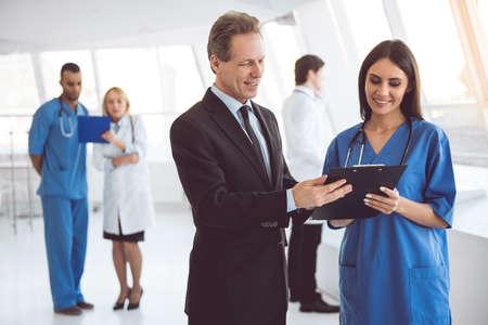 ハンサムな中高年ビジネスマンと美しい若い医師を書類を議論し、病院のホールに立ちながら笑顔 写真素材