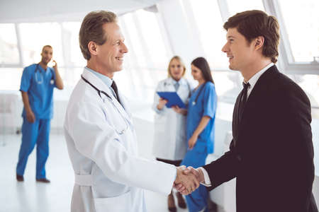 Handsome mature doctor and young businessman are shaking hands and smiling while standing in the hospital hall Stock Photo