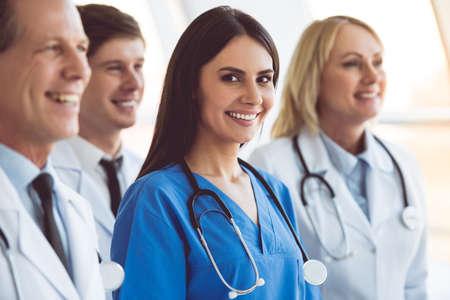 El equipo acertado de médicos está sonriendo mientras que se coloca en hospital. El doctor joven hermoso está mirando la cámara Foto de archivo - 72130007