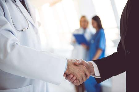 잘 생긴 성숙한 의사와 병원 복도에 서있는 동안 악수하는 젊은 사업가의 잘린 된 이미지 스톡 콘텐츠