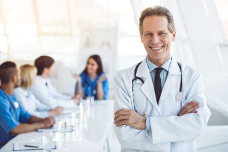 Handsome mature medical doctor is looking at camera and smiling while his colleagues are sitting in the background Stock Photo