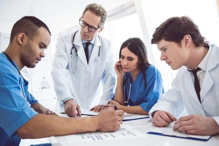 성공적인 의사는 회의 도중 진단을 논의하고 있습니다.