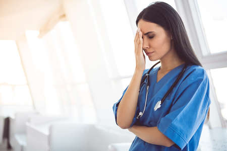 Beautiful doctor in blue scrubs is covering her face while standing in hospital corridor Foto de archivo