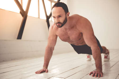 sixpack: Handsome muscular man with bare torso is doing push-ups