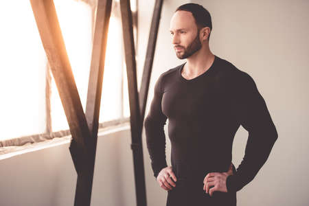 close fitting: Portrait of handsome muscular man in black close-fitting jumper looking out the window