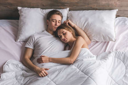 Top view of beautiful young couple hugging while sleeping together in bed at home Reklamní fotografie