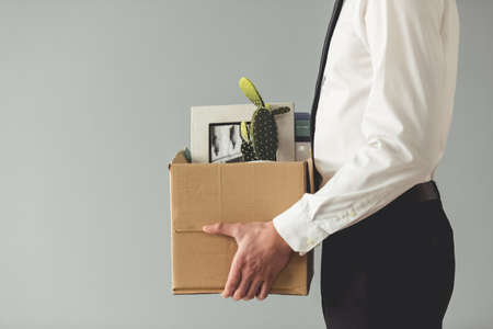 Getting fired. Cropped image of handsome businessman in formal wear holding a box with his stuff, on gray background
