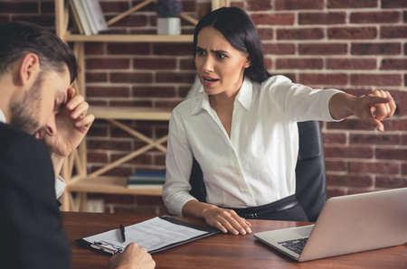 De mooie vrouwelijke werkgever vuurt jonge zakenman af en wijst weg terwijl het zitten in haar bureau Stockfoto