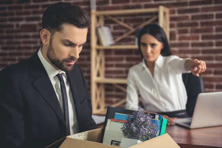 Getting fired. Handsome businessman in suit is holding a box with his stuff, woman in the background is pointing away Banque d'images