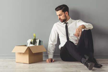 Getting fired. Handsome businessman in formal wear is sitting on the floor near the box with his stuff, on gray background
