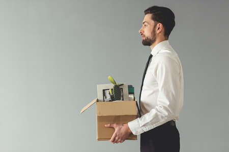 Getting fired. Side view of handsome businessman in formal wear holding a box with his stuff, on gray background Stock Photo