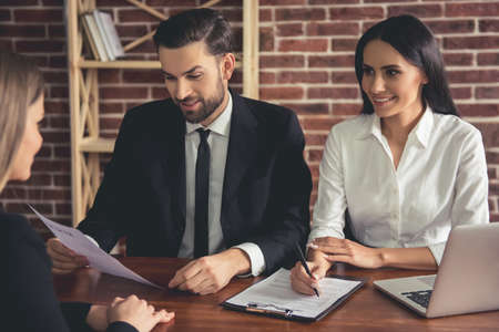 Beautiful couple of employers in suits are conducting a job interview while sitting in office Stock Photo
