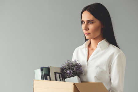 Getting fired. Beautiful young business woman is holding a box with her stuff and looking sadly, on gray background Stock Photo