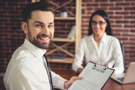 Handsome employee in suit is holding a resume, looking at camera and smiling during the job interview