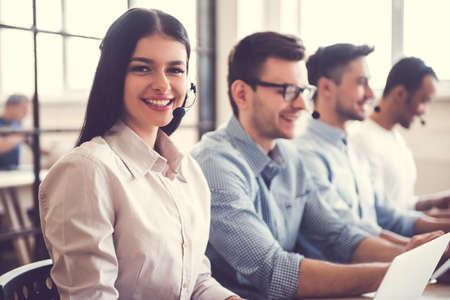 ヘッドセットで美しいビジネス人々 はコンピューターを使用していて、office で作業しながら笑みを浮かべてします。女の子がカメラを目線します。