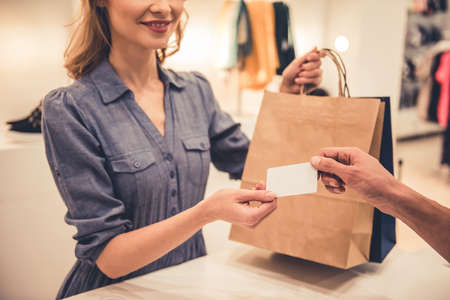 Il bellissimo assistente del negozio sorride mentre dà acquisti e carta di credito a un cliente bello Archivio Fotografico