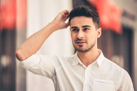 Handsome guy is scratching head while doing shopping in the mall Stock Photo - 74025266