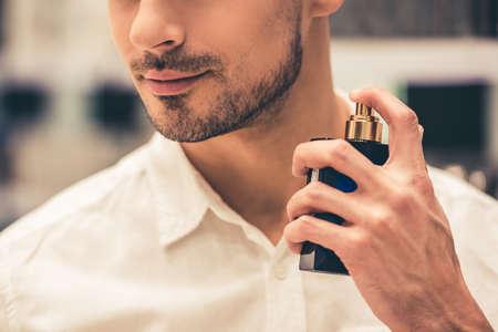 Przystojny facet wybiera pachnidła i ono uśmiecha się podczas gdy robiący zakupy w centrum handlowym Zdjęcie Seryjne