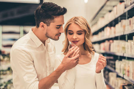 Beautiful couple is choosing perfumes and smiling while doing shopping in the mall