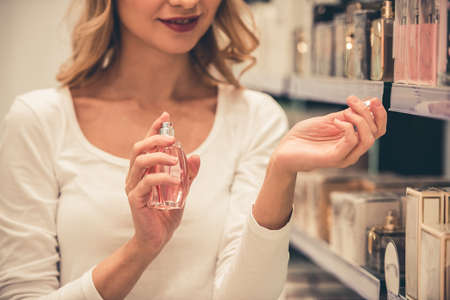 Beautiful girl is choosing perfumes and smiling while doing shopping in the mall