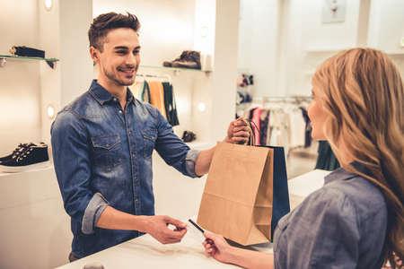 De knappe winkelmedewerker glimlacht terwijl het geven van aankopen en creditcard aan mooie cliënt Stockfoto