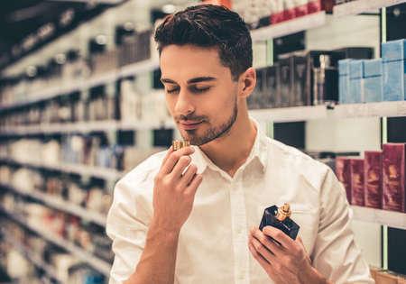 ハンサムな男は香水を選択してショッピング モールでのショッピングをしながら笑みを浮かべて 写真素材