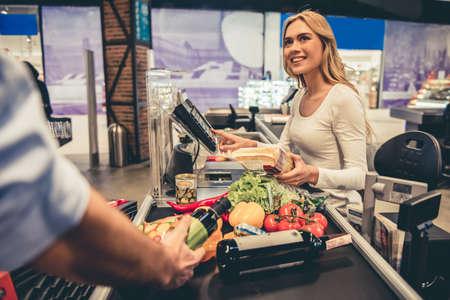 美しい若いレジはスーパーで働きながら笑っています。