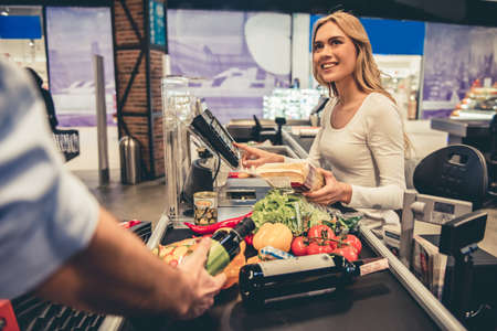 Beautiful young cashier is smiling while working at the supermarket