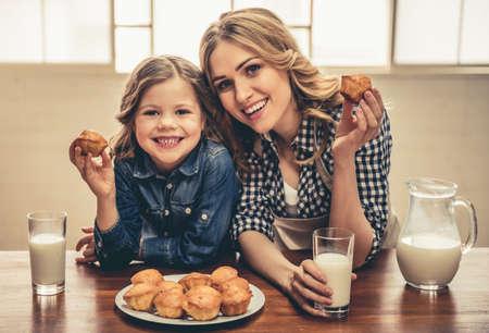 귀여운 소녀와 그녀의 아름 다운 젊은 엄마는 카메라를보고 집에서 쉬고있는 동안 웃 고 우유와 함께 머핀을 먹고있다