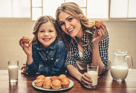 Cute little girl and her beautiful young mom are eating muffins with milk, looking at camera and smiling while resting at home
