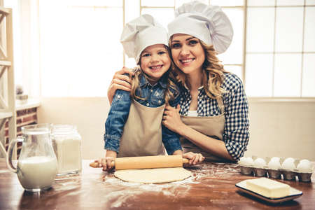 Cute little girl and her beautiful mom in aprons and chef hats are smiling while flattening the dough using a rolling pin in the kitchen