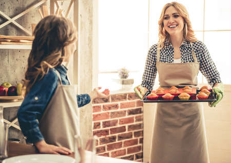 Cute little girl and her beautiful young mom are smiling while having their muffins baked
