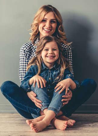 かわいい女の子と彼女の美しい若いお母さんが一緒に床に座って、カメラ目線と笑顔、灰色の背景に