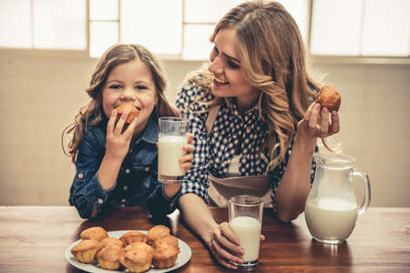 Cute little girl and her beautiful young mom are eating muffins with milk and smiling while resting at home