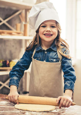 Cute little girl in apron and chef hat is looking at camera and smiling while flattening the dough using a rolling pin in the kitchen