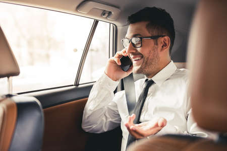 Handsome businessman in suit and eyeglasses is talking on the mobile phone and smiling while sitting on back seat in the car