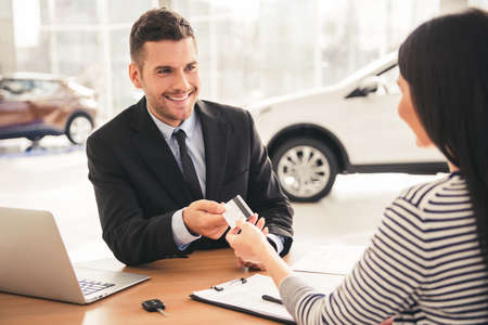 finance manager: Visiting car dealership. Handsome sales manager is taking a credit card from the client and smiling