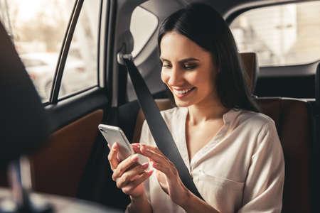 Hermosa mujer de negocios está utilizando un teléfono inteligente y sonriente mientras está sentado en el asiento trasero en el coche Foto de archivo